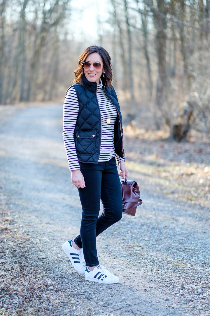 Jo-Lynne Shane wearing black J.Crew Excursion quilted down vest with striped tissue turtleneck, AG the legging ankle jeans, and Adidas Originals Superstar. #fashion #womensfashion #winteroutfit