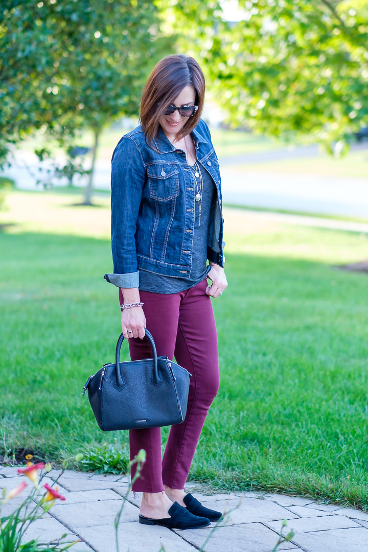 Jo-Lynne Shane styling burgundy jeans with a denim jacket and slide loafers