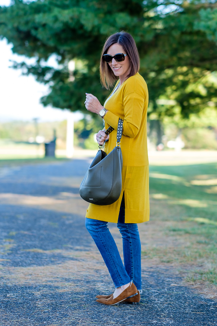 Jo-Lynne Shane wearing a mustard cardigan outfit with moss green bag and cognac loafers.