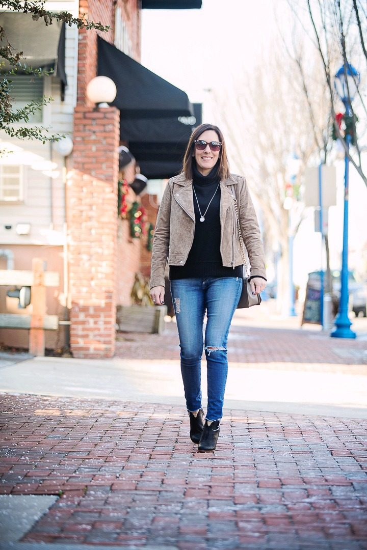 How to Wear Suede Moto Jacket for Winter: Winter Outfit with BlankNYC taupe suede moto jacket over black turtleneck with AG raw hem ankle legging jeans and Rag & Bone Margot booties.