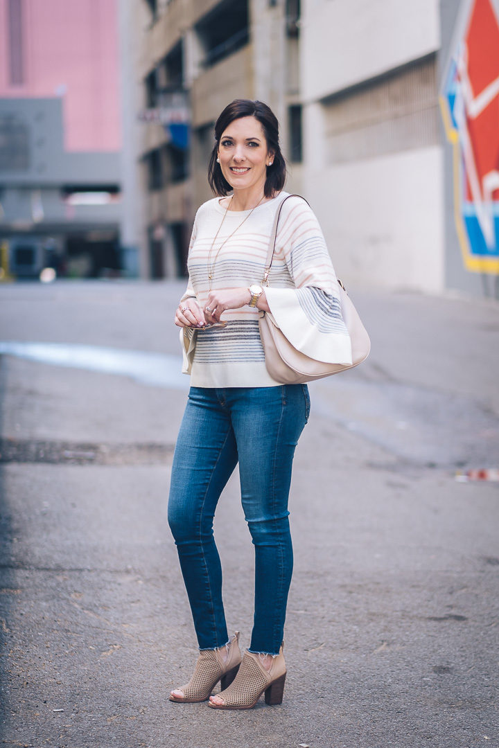 A dressed-up casual spring outfit featuring LOFT mixed stripe bell sleeve sweater with AG raw hem legging ankle jeans and Vince Camuto perforated peep toe booties. Also wearing kate spade new york mylie hobo.