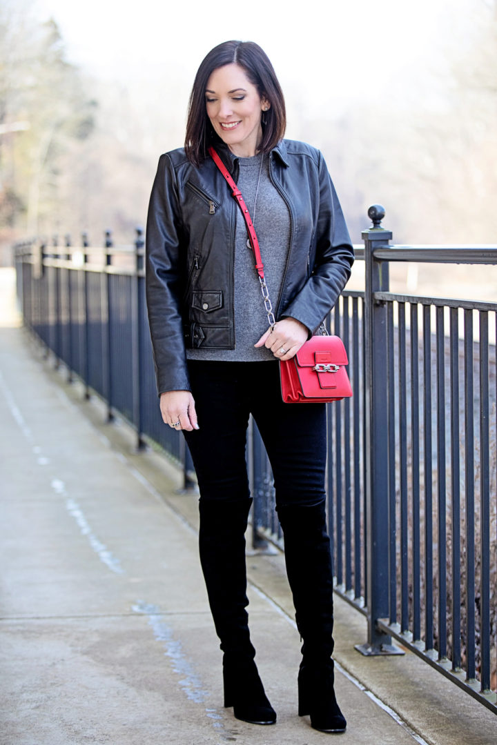 Jo-Lynne Shane styling a winter date night outfit with a leather jacket, suede over the knee boots, black jeans, a grey cashmere sweater, and a red bag... Click through to see how it came together!